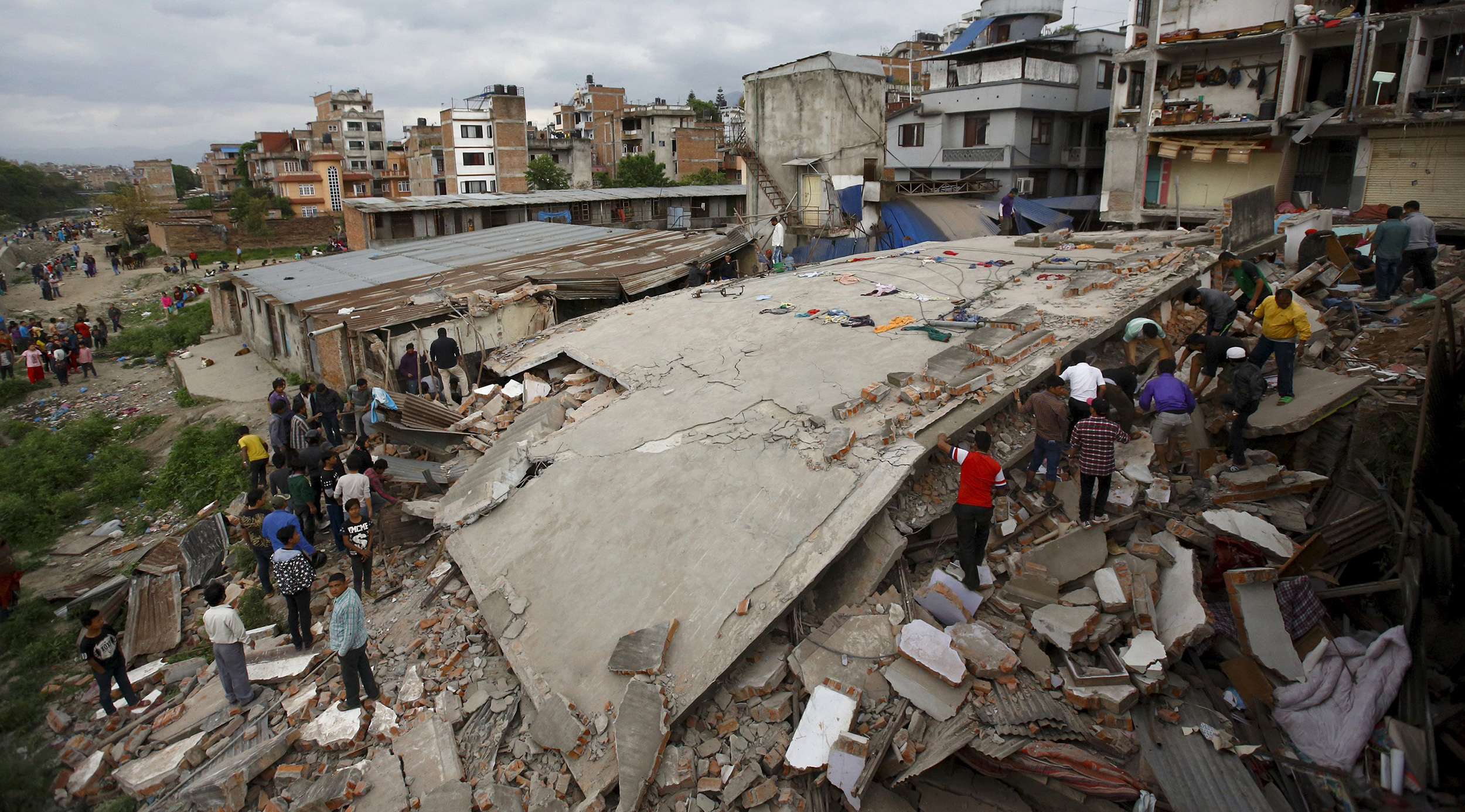 Image: People gather near a collapsed house after major earthquake in Kathmandu